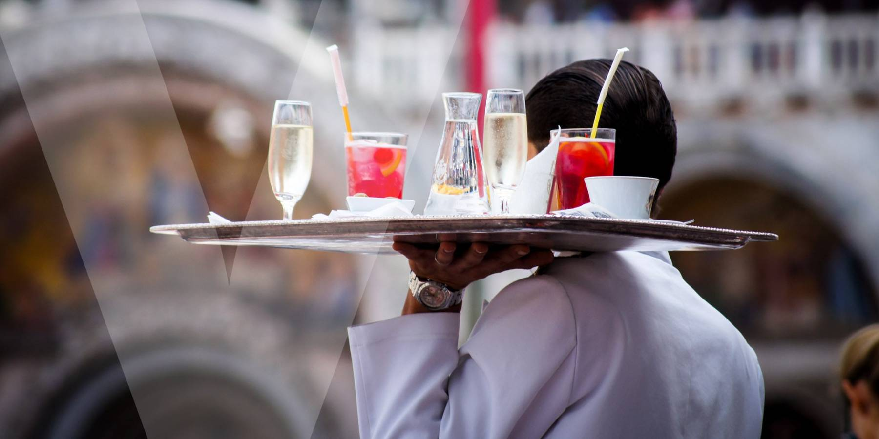 A waiter carrying a service plate full of beverages