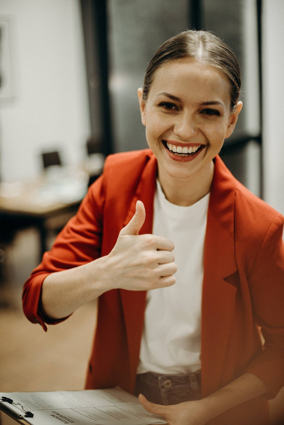 A woman smiling and giving the thumbs up