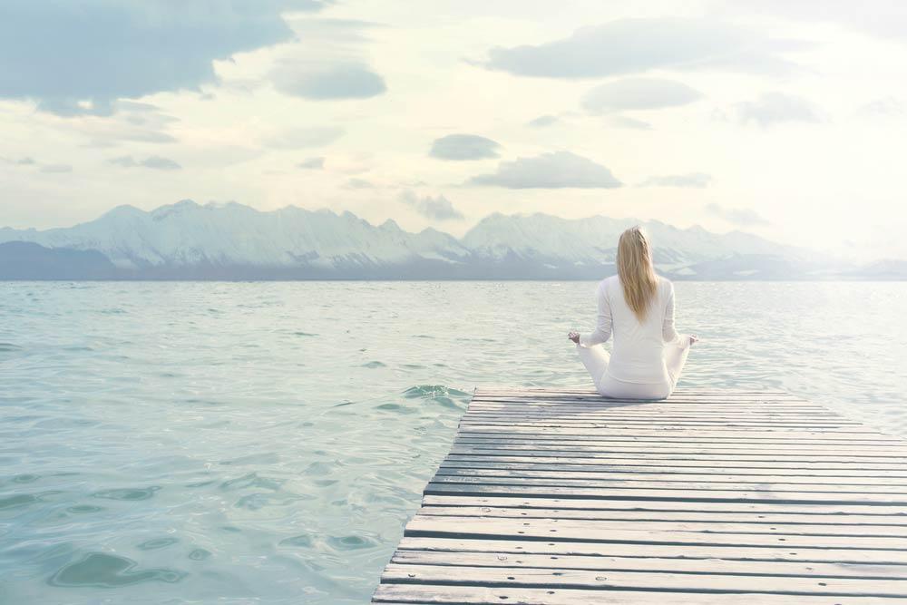 woman meditating above sea