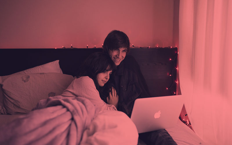 A couple sitting on a bed using a laptop