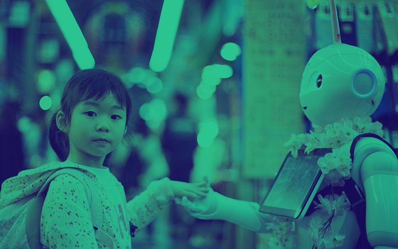 Little girl holding a robots hand