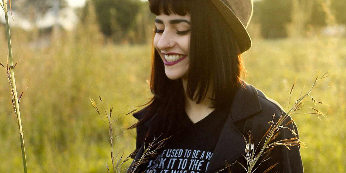 A happy person smiling in a sun lit feild