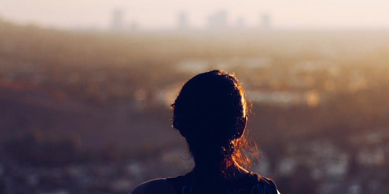 Silhouette of some one looking toward a city at day break