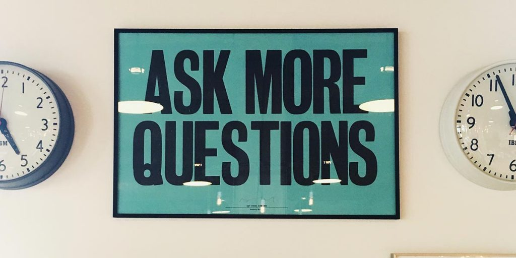 """Plaque saying """"Ask More Questions"""""""
