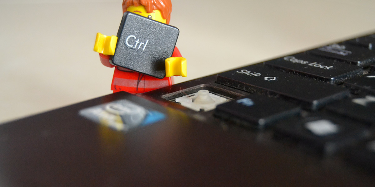 A lego figure removing the CTRL key from a computer keyboard