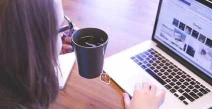 A person drinking Tea and using a laptop