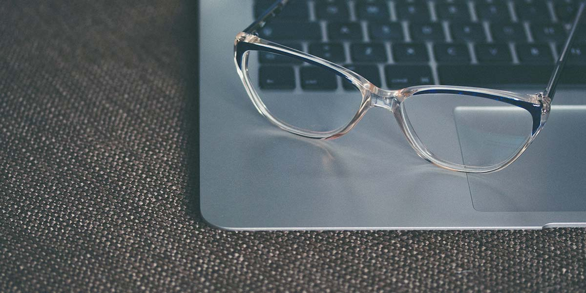 A pair of glasses resting on a laptop
