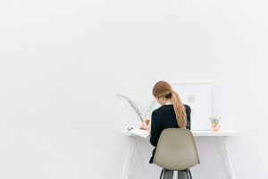 Girl working at a desk in a sparse white room