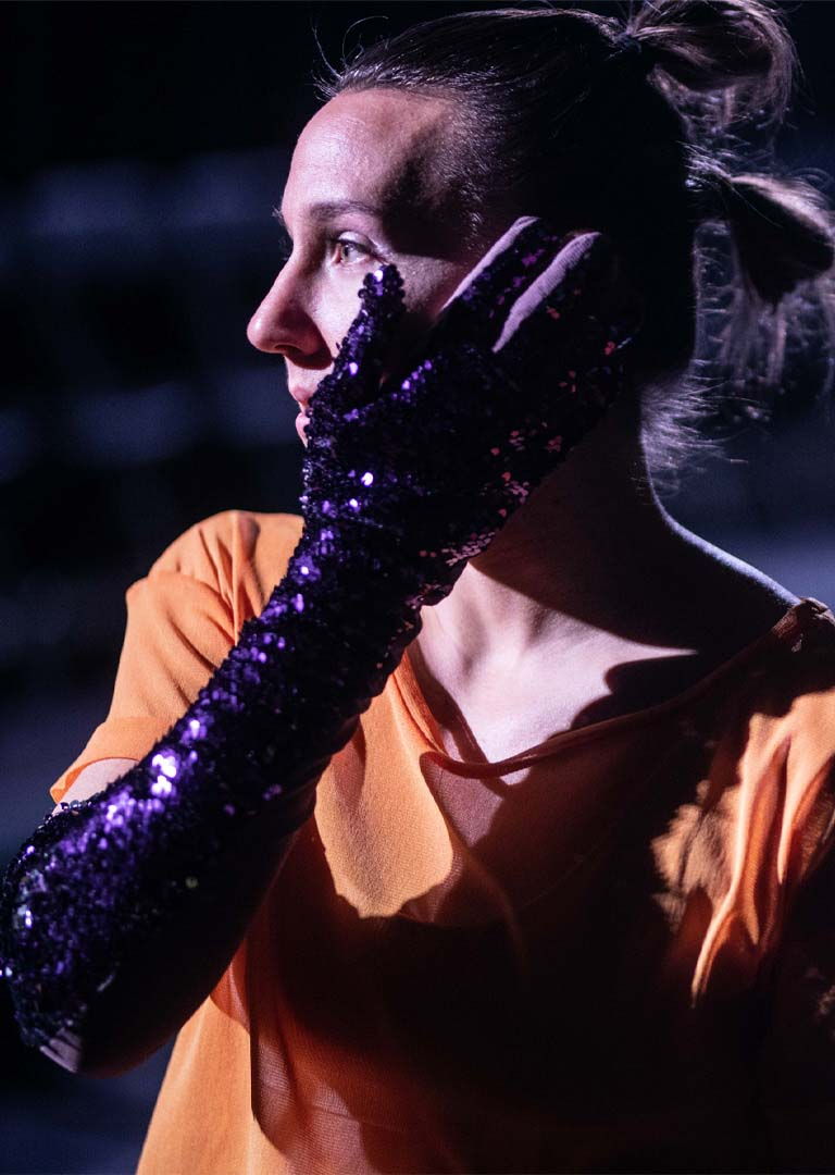 Anna Kempin performing in Vox contemporary dance, wearing purple glitter glove and looking towards the audience