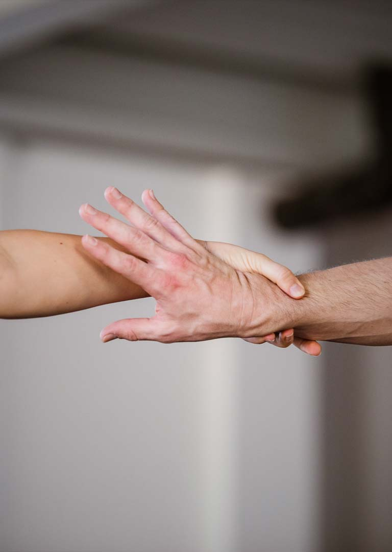 Anna Kempin is tightly holding another hand and having a tight grip, during Tanz Netz Freiburg dance workshop