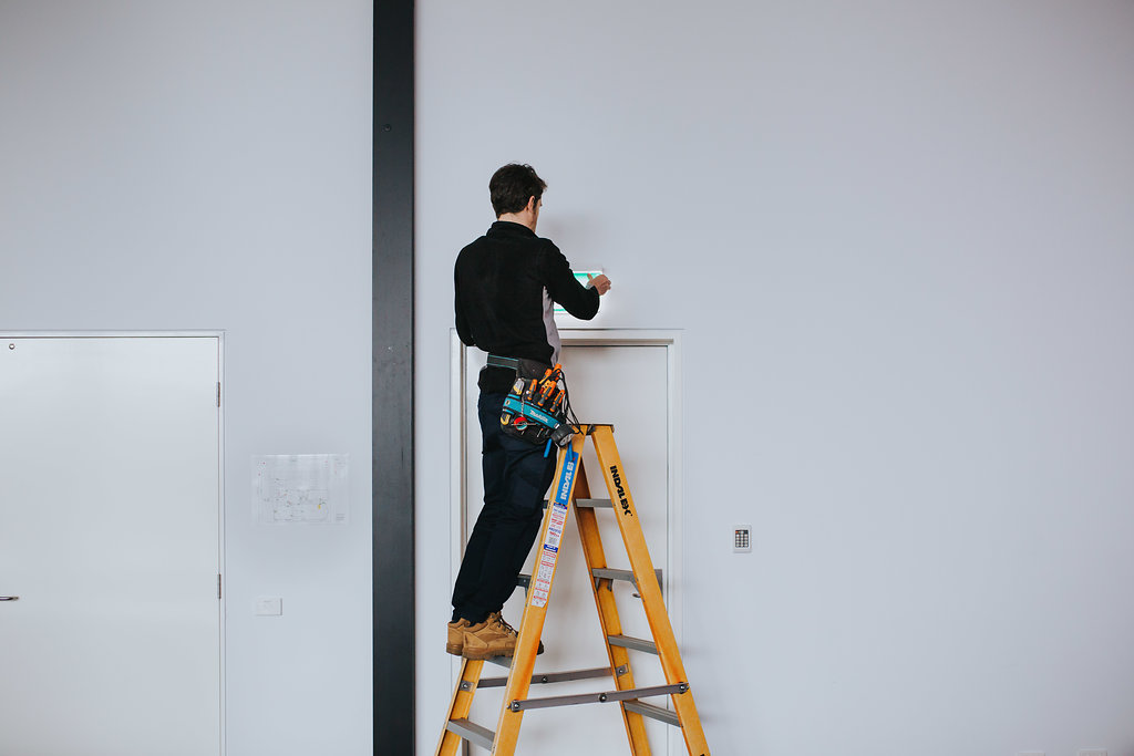 Electrician up on ladder replacing a security light.