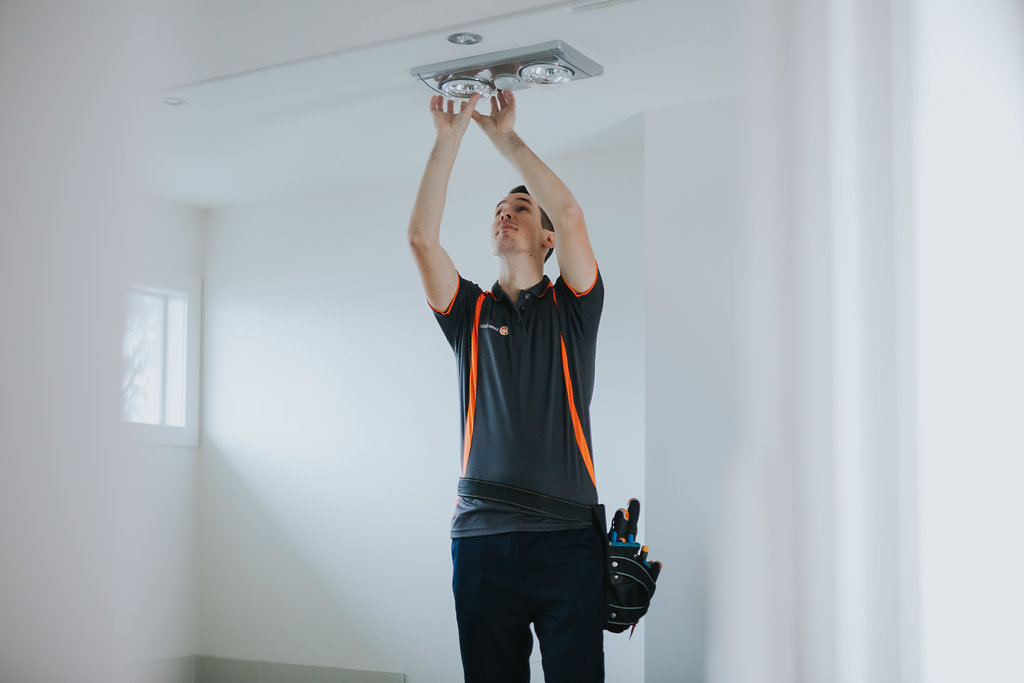 An electrician fixes a bathroom heat exhaust fan