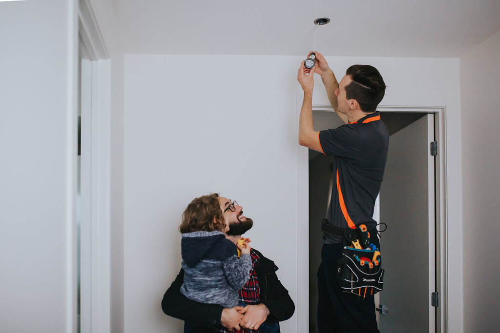 Electrician changing light bulb while family watches on