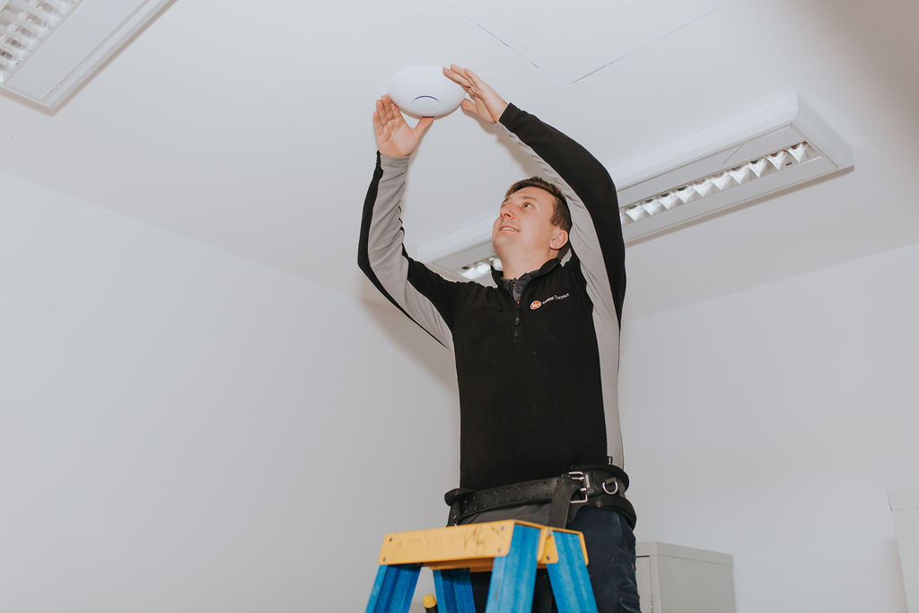 Electrician installs wireless access point
