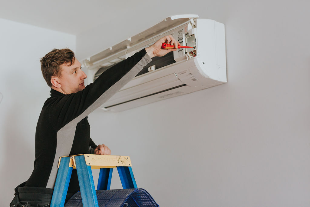 Electrician installing a reverse cycle air conditioner