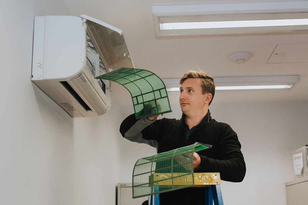 Electrician servicing a reverse cycle air conditioner