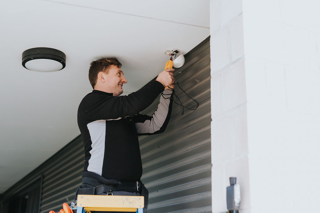 Electrician installing a movement sensor for security lights