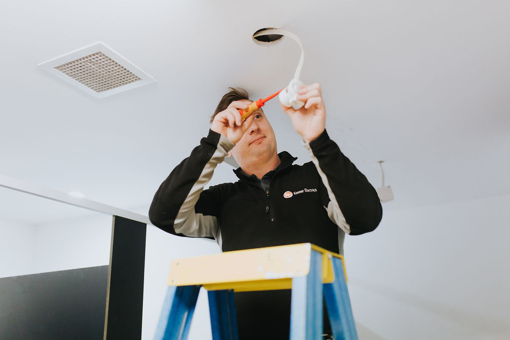An electrician repairing a light fitting