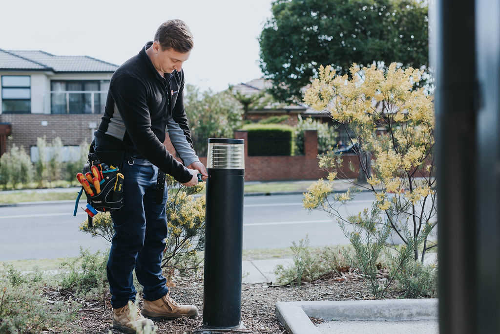 Electrician installing outdoor lighting bollard