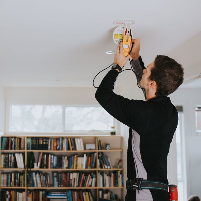 Electrician installing a Clipsal photoelectric smoke alarm