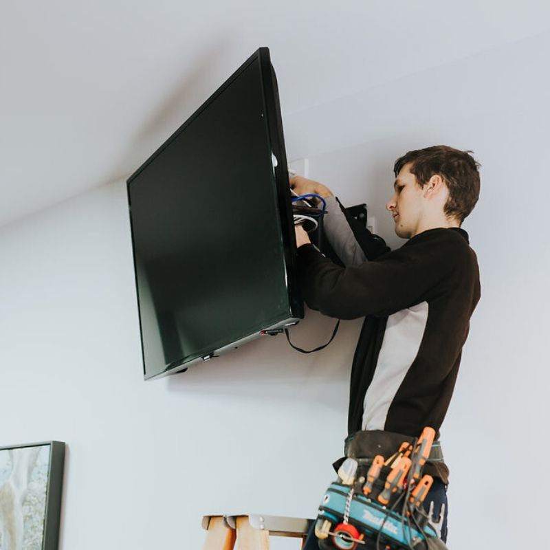 Electrician installing a wall mount TV for home audio visual