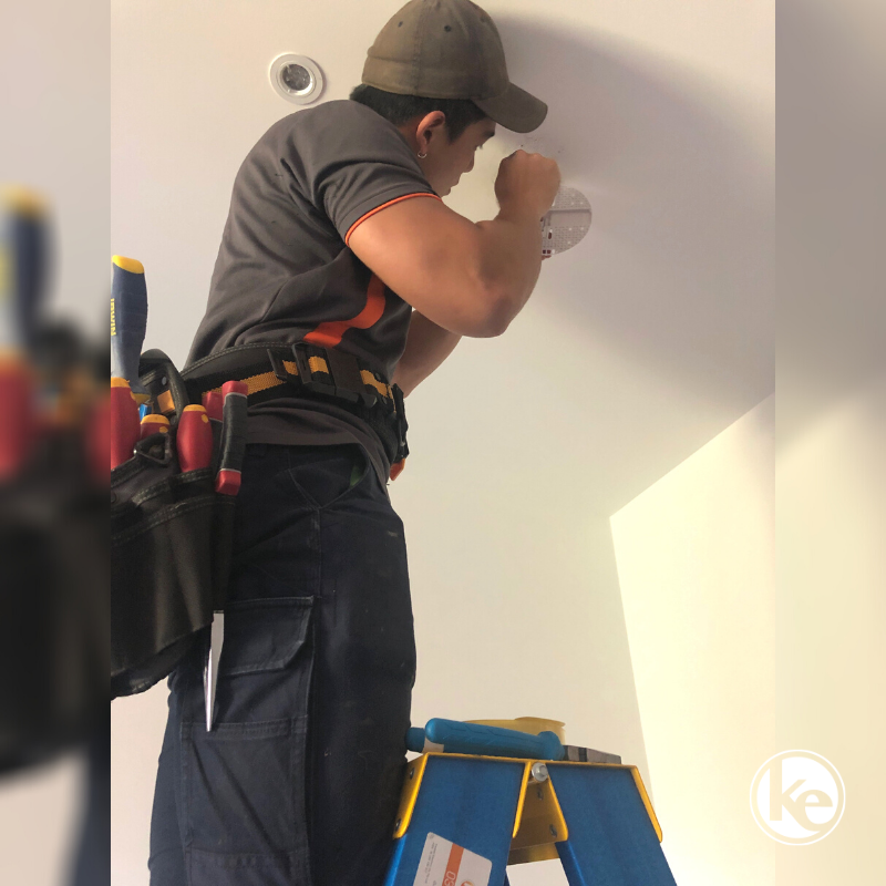 Electrician installing interconnected smoke alarm to protect from fire risk