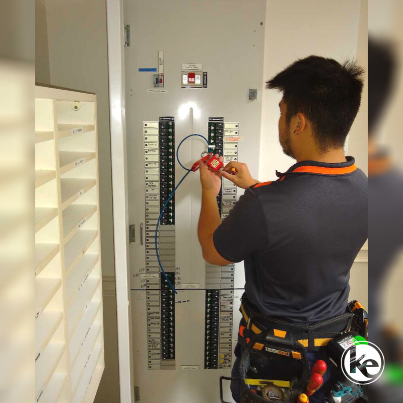 Licensed electrician doing electrical compliance testing on commercial switchboard