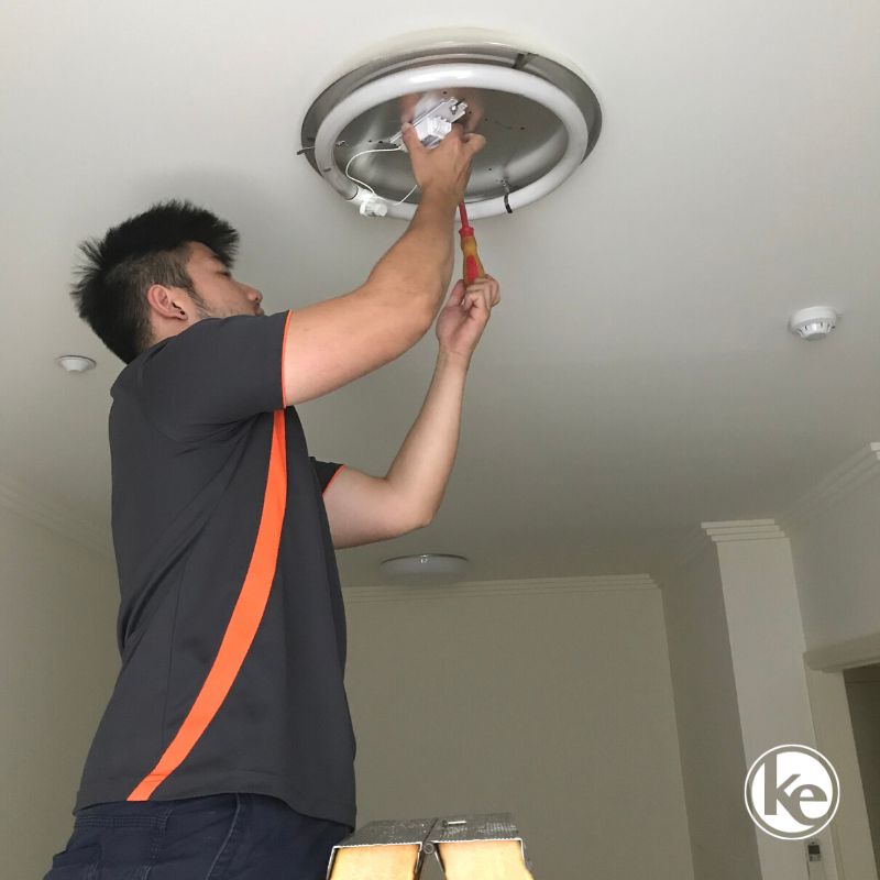 Reliable electrician installing a new LED oyster light