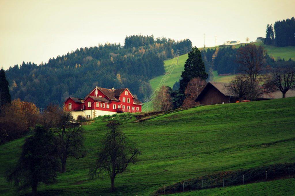 Big red barn house on green mountain