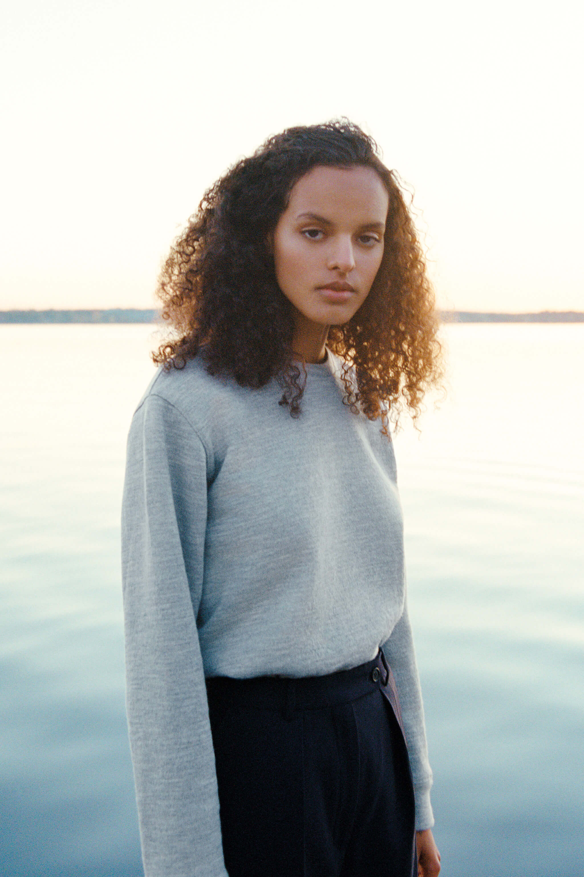A woman of Swedish-African descent wearing a sweatshirt looks into the camera with the Stockholm archipelago in the background