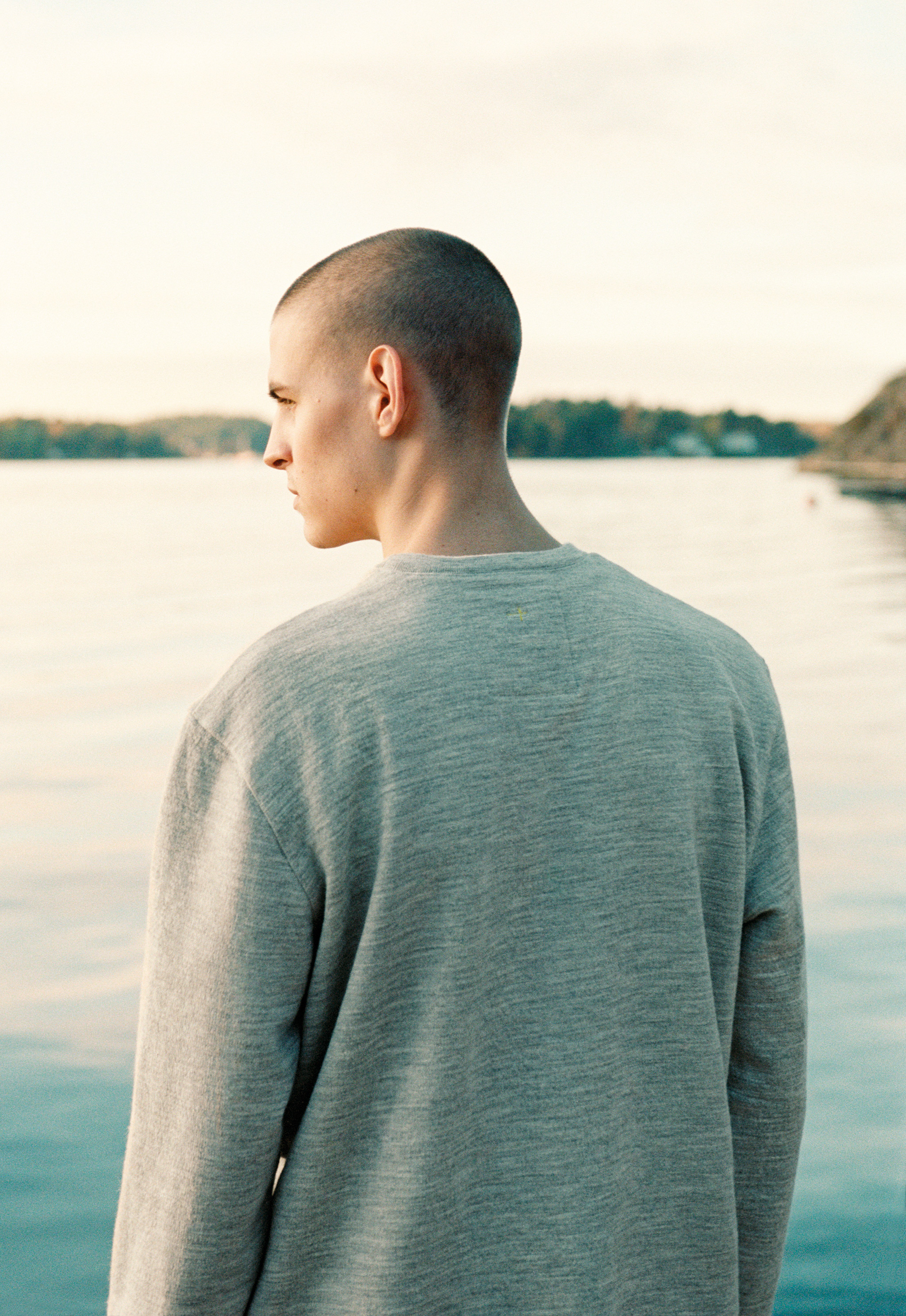A back view of a man of white Swedish descent wearing a grey sweatshirt, with a yellow embroidered Nordic cross just below his neck