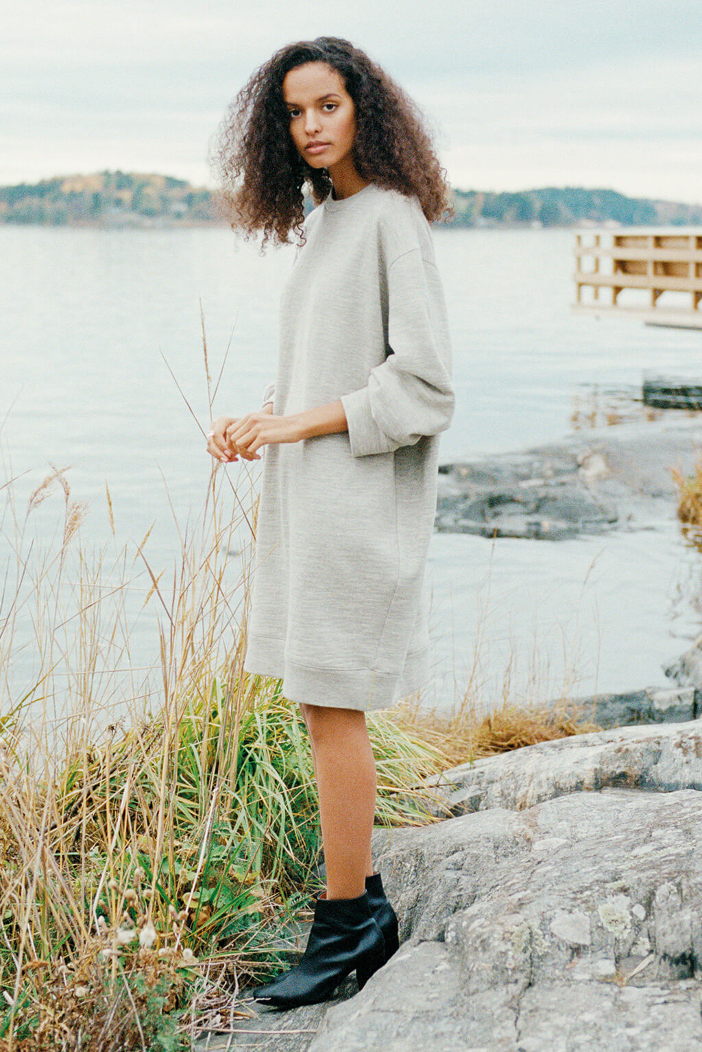 A woman of Swedish-African descent wearing an oversized sweatshirt dress that ends just above her knees looks into the camera, playing with reeds by the water. She is wearing the sweatshirt and a pair of ankle-high boots