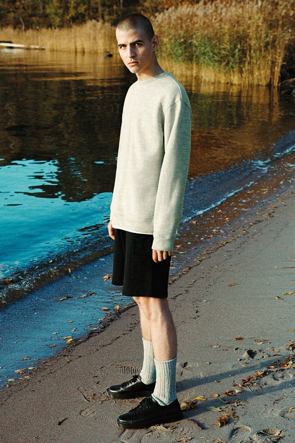 A man with a shaved head of white Swedish descent, wearing a grey sweatshirt, looks into the camera whilst standing on a beach. He is wearing shorts, woollen socks and black shoes