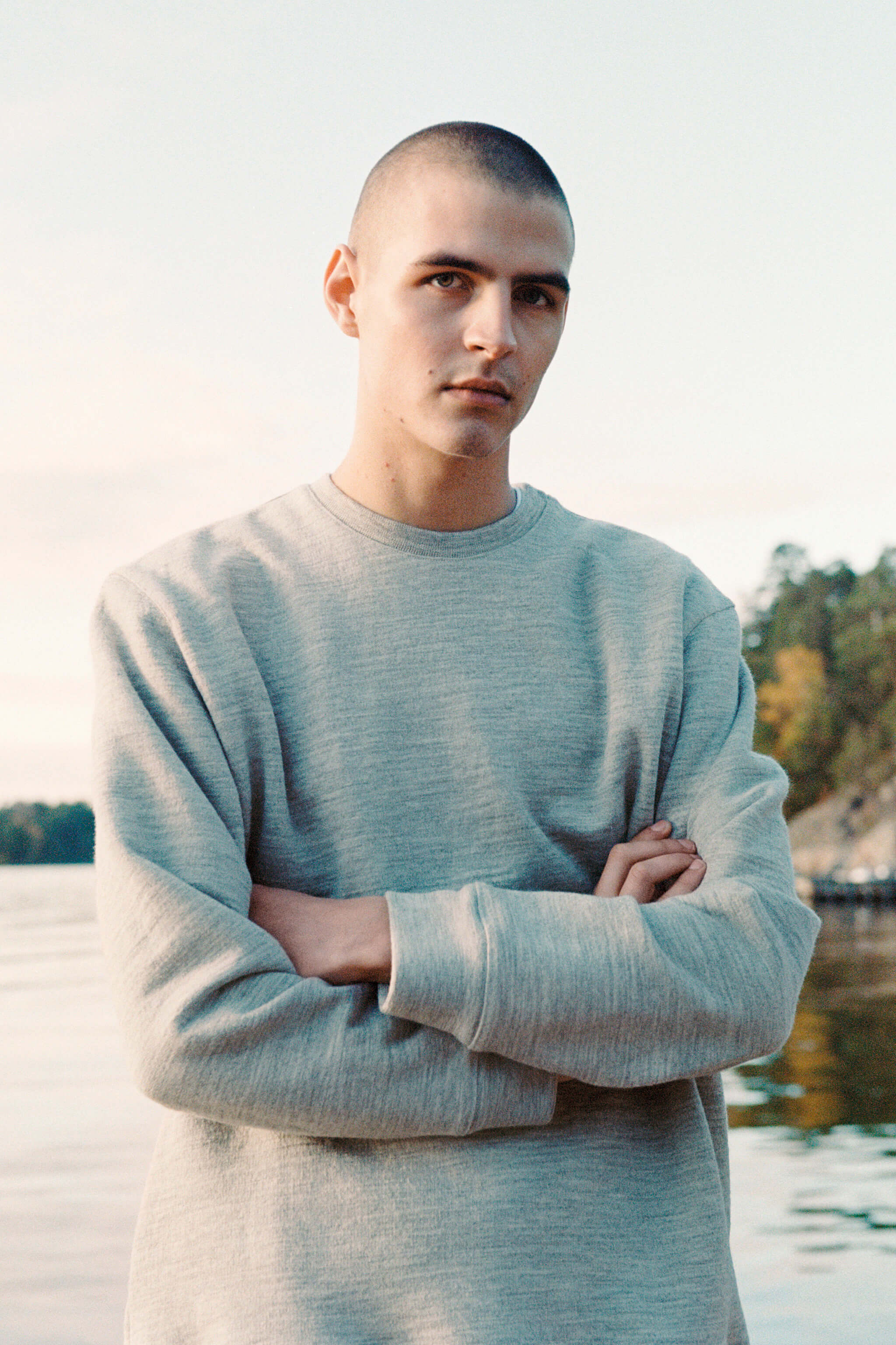 A man with a shaved head of white Swedish descent wearing a grey sweatshirt looks into the camera with his arms folded