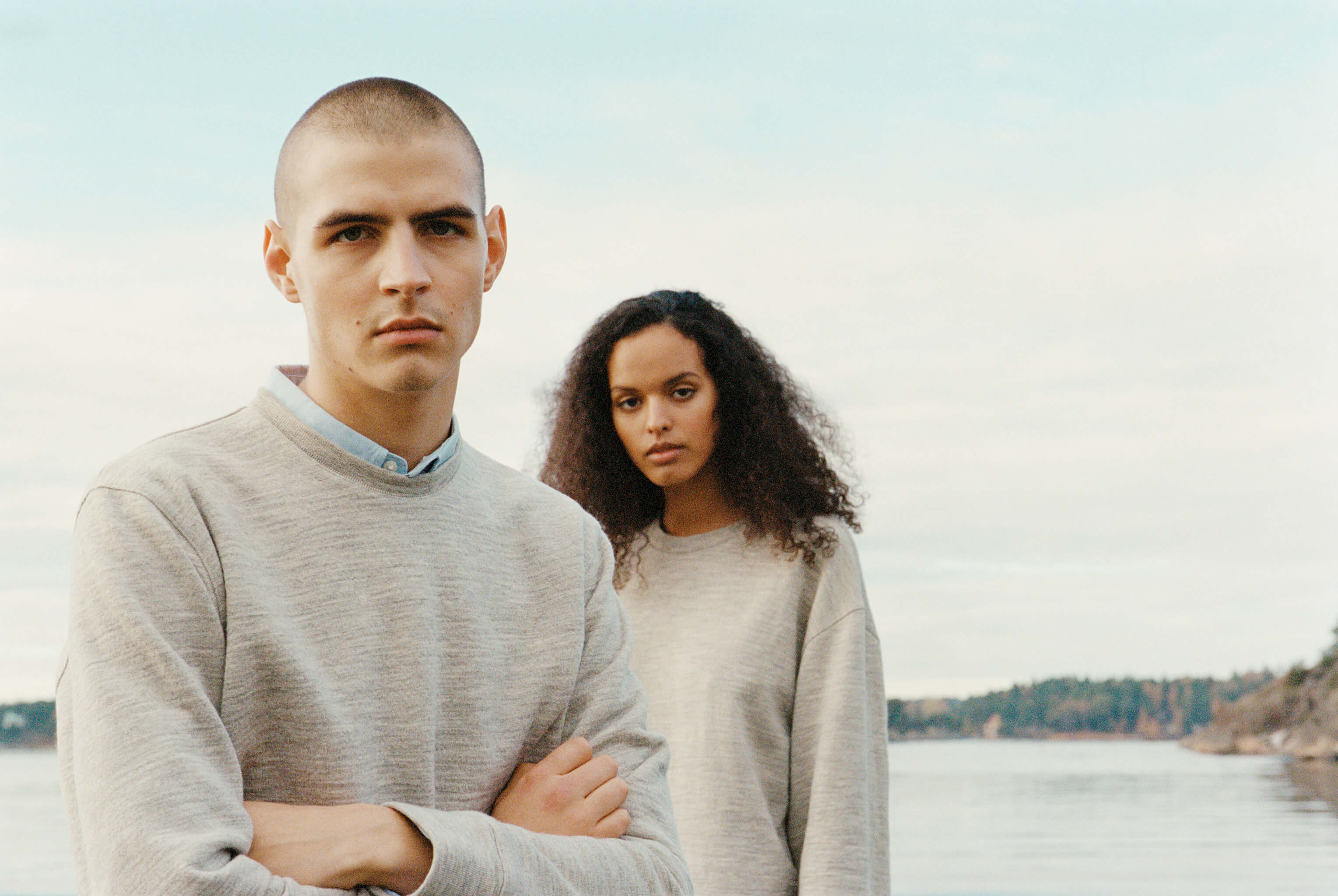 A shaved-head man of white Swedish descent a woman of Swedish-African descent in grey sweatshirts are standing by the Stockholm archipelago, looking at the viewer