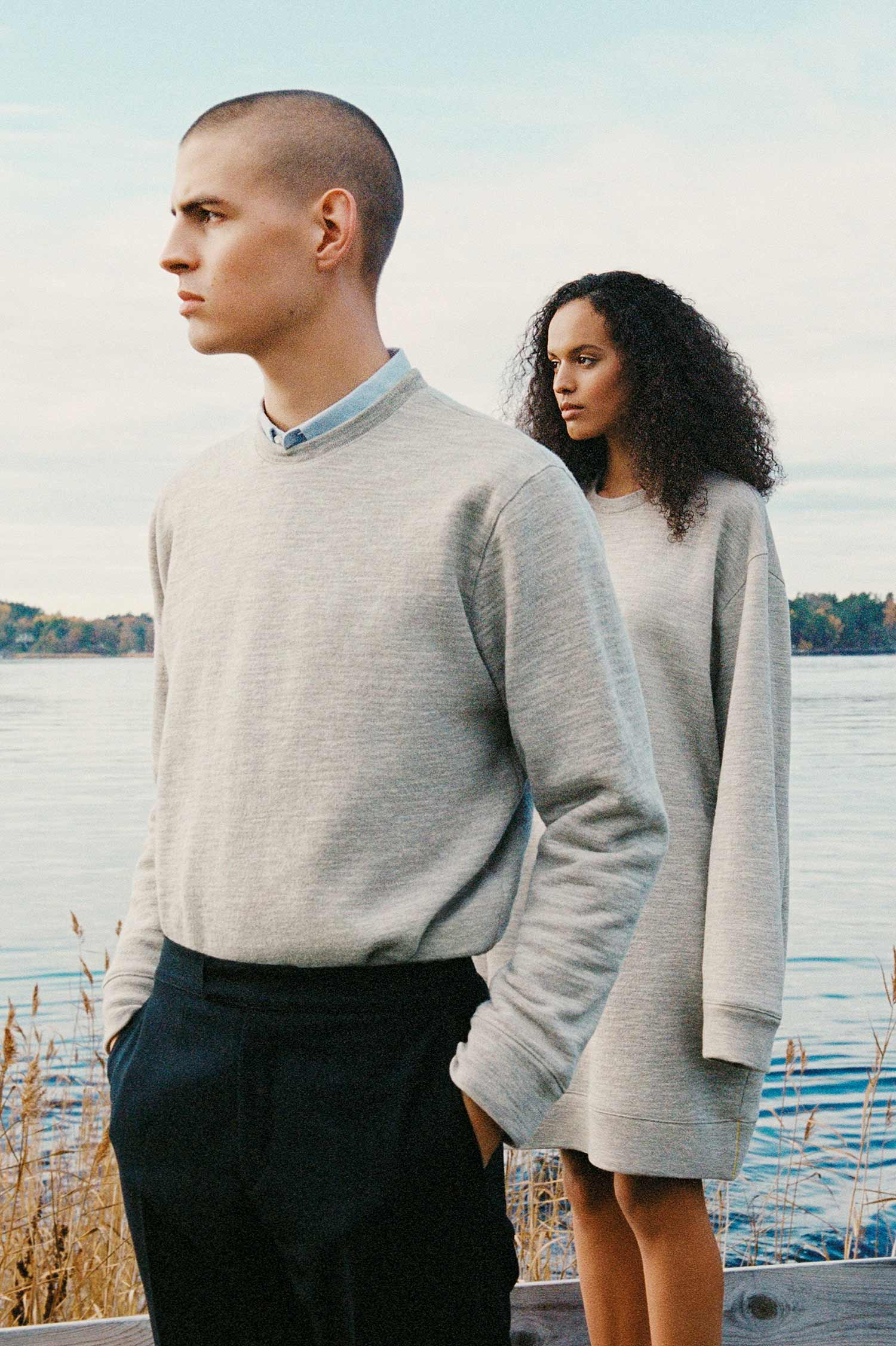 A man with a shaved head of white Swedish descent and a woman of Swedish African descent stand side by side, wearing grey sweatshirts made from 100% Swedish wool, looking into the distance, against water of a lake in the Stockholm archipelago