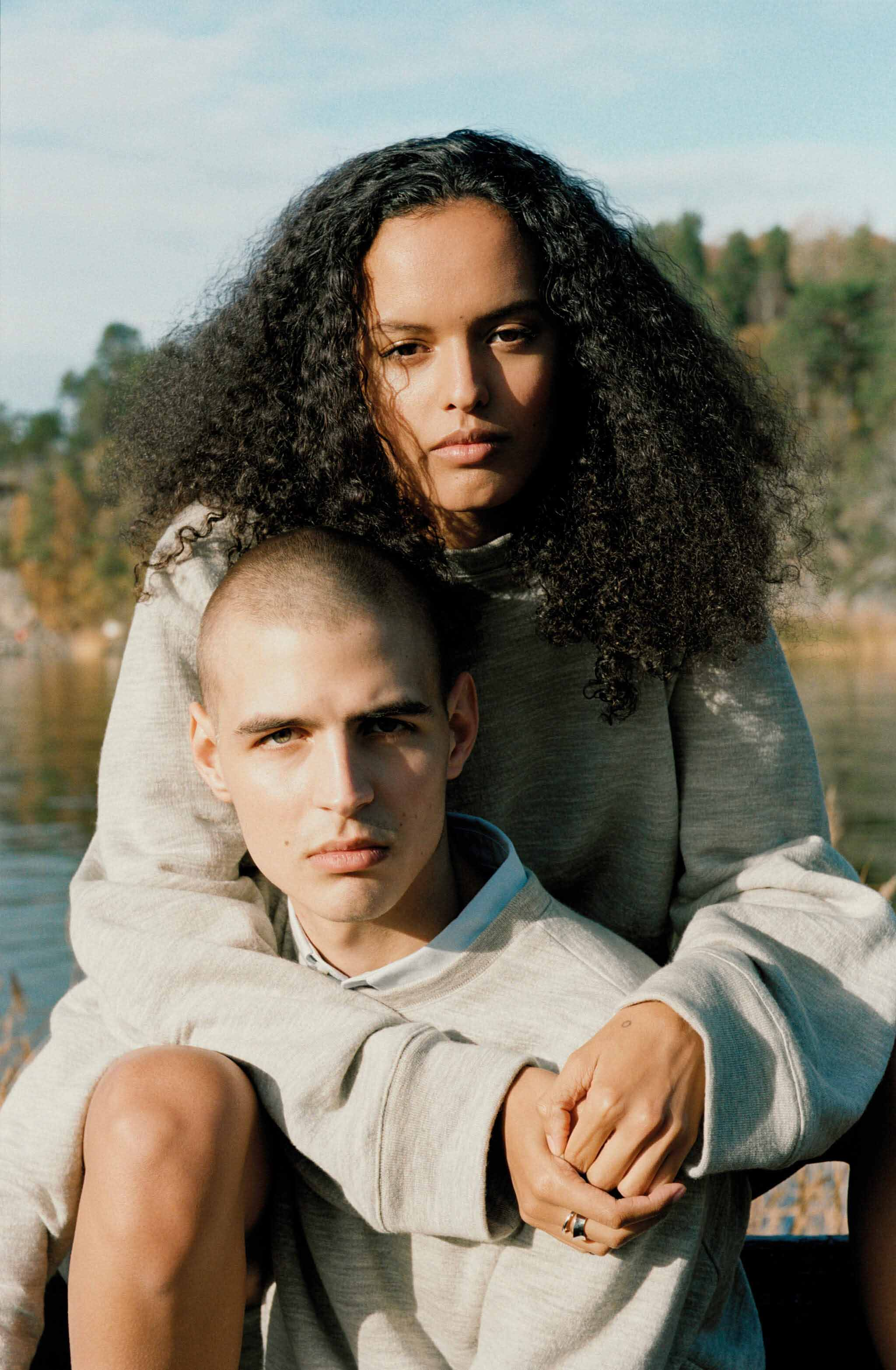 A woman of Swedish-African descent and a man of white Swedish descent wearing grey, sustainably made sweatshirts, posing in front of a body of water in Värmdö, Sweden