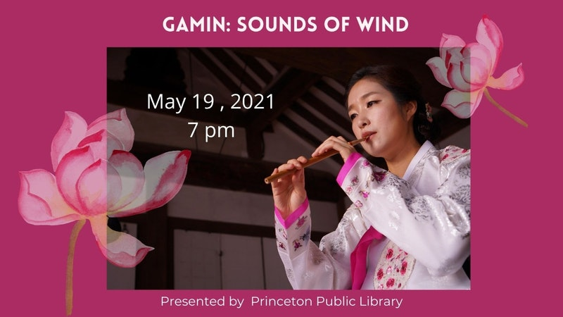 gamin, a performer of traditional Korean music, playing a piri (double reed Korean oboe). She is wearing traditional Korean clothing.
