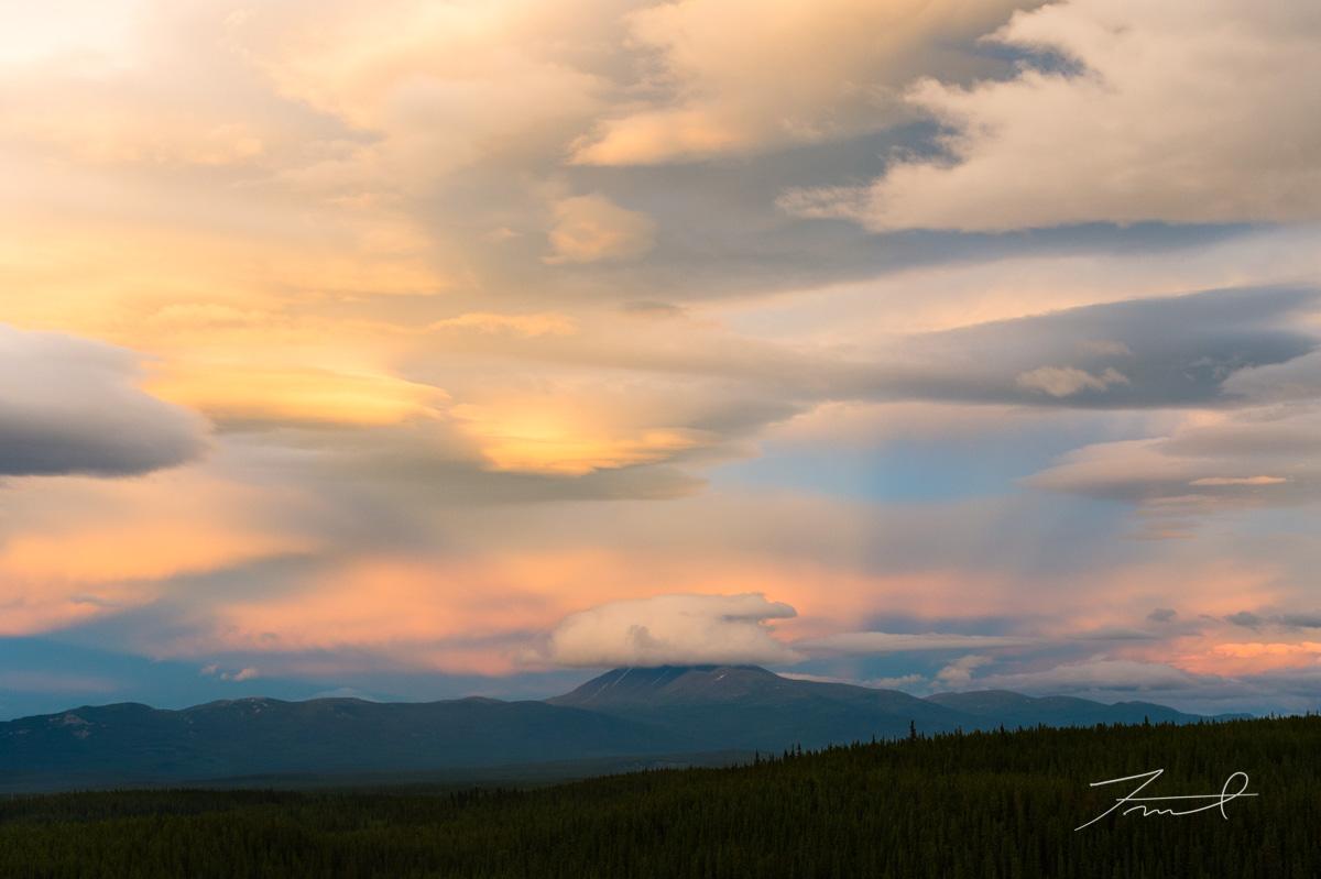 夕日が作る光芒が空を青とオレンジのグラデーションで染める