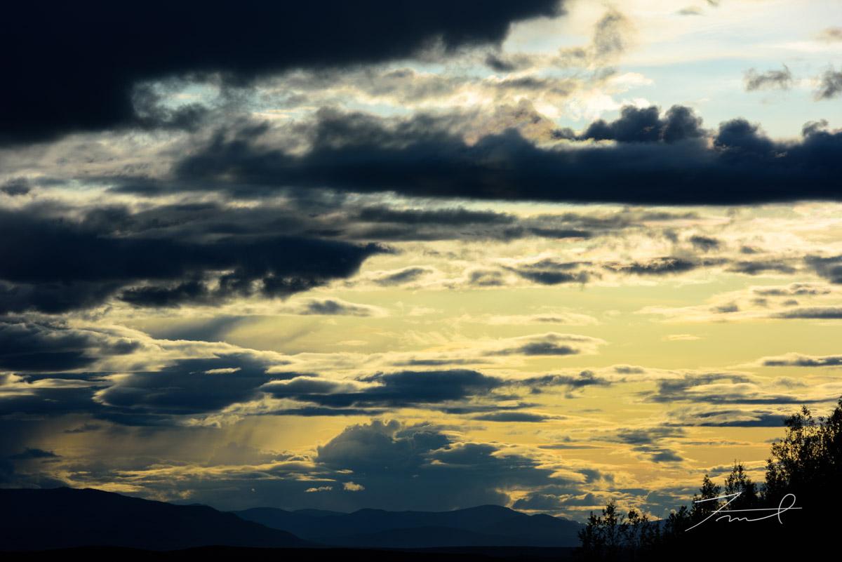 夕日で黄金色から薄青色のグラデーションに色づいた空に雨雲が浮かぶ
