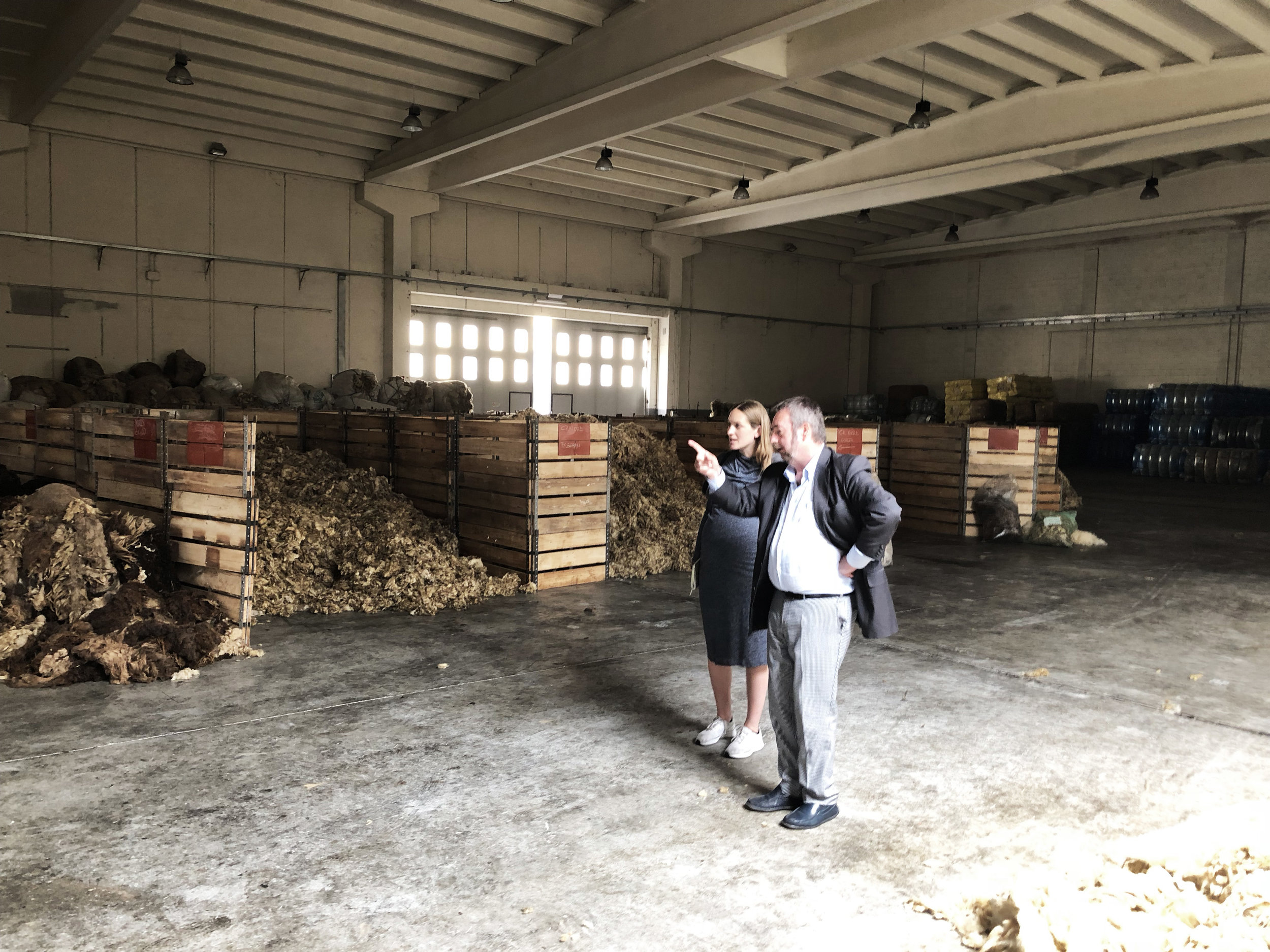Nigel and Lisa stand in the middle of a sorting shed amongst piles of unsorted wool
