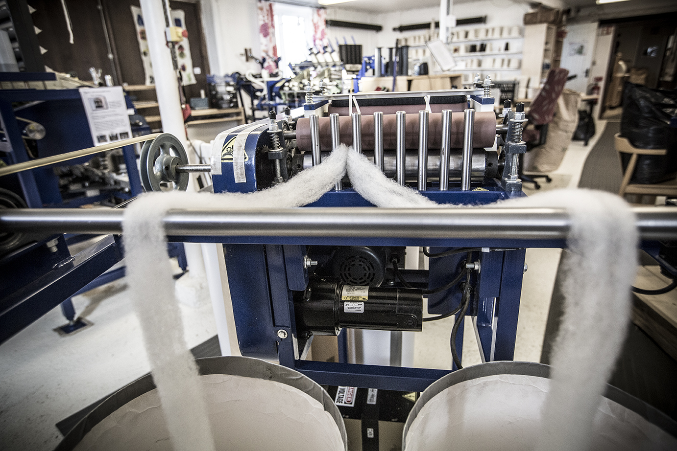 Two streams of fluffy wool tops are coming from a machine in a small factory