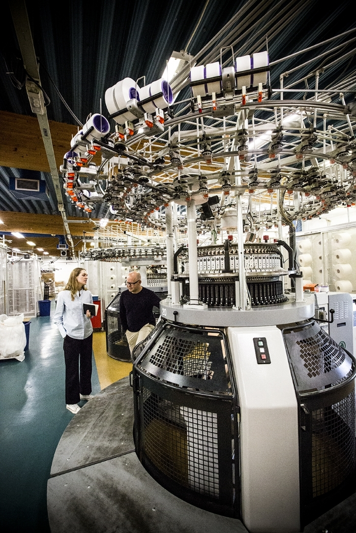 A woman, Lisa, and a man, Jonas Lorentzon, are standing by a huge, circular machine that towers over them. The machine has spools of thread connected to it, and is preparing to knit material.