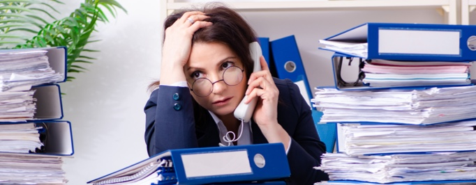 Woman sitting at desk surrounded by paperwork