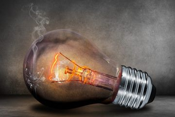 A lightbulb with smoke coming out of top