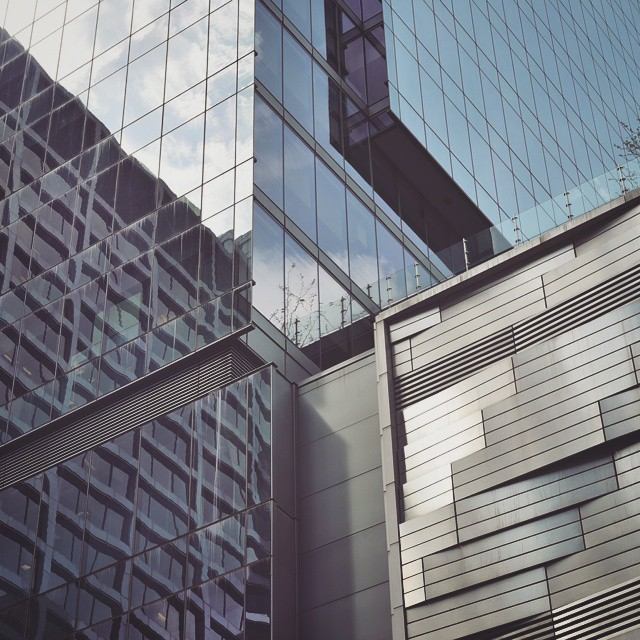 Photo of intersecting lines and reflections of buildings in downtown Chicago, creating an abstract geometric image, having a blue/silver tint and varying textures