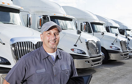 Truck driver and a row of white semi trucks