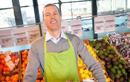Grocery employee stocking fruit