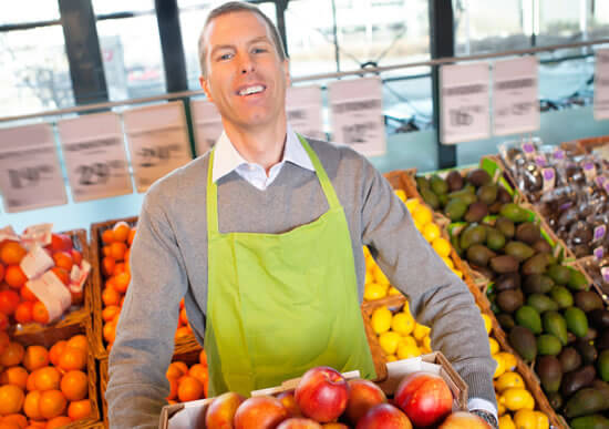 Grocer stocking fruit in the produce aisle