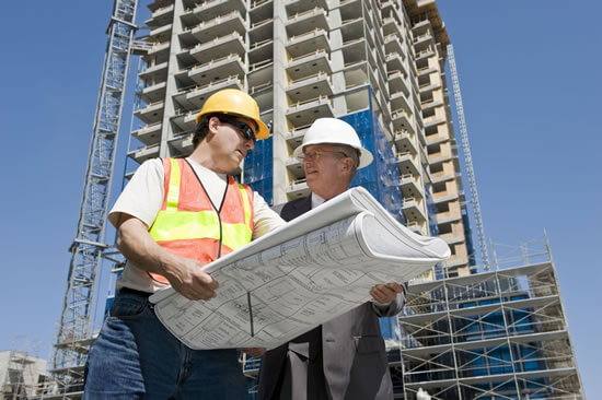 Construction manager reviewing blueprints with architect